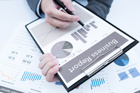 Close-up of graphs and charts analyzed by businessman photo
