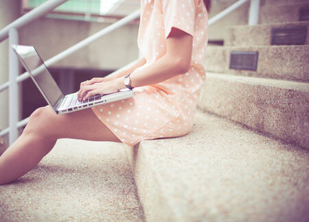 Young woman using laptop on steps outdoors photo