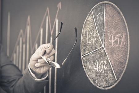 Side view of a businessmans hand. Business graph on a blackboard. photo
