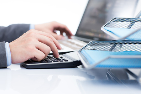 Businessman analyzing investment charts with laptop. Accounting Stock Photo