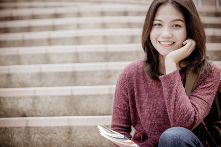 college campus: attractive female college student sitting on stairs
