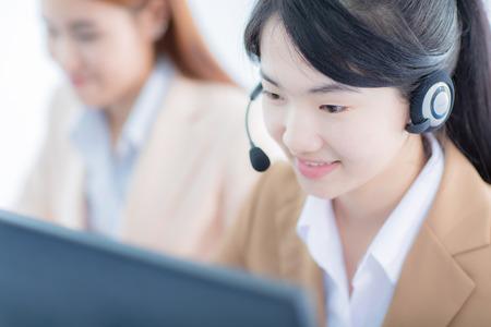 computer centre: Las mujeres asi�ticas centro de llamadas con los auriculares del tel�fono Foto de archivo