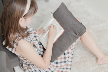 Beautiful young woman writing something in the note pad while lying on the floor at living room Stock Photo