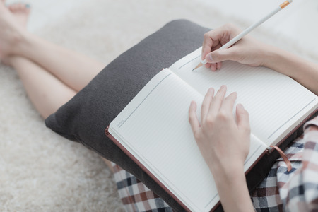 note book: Beautiful young woman writing something in the note pad while lying on the floor at living room Stock Photo