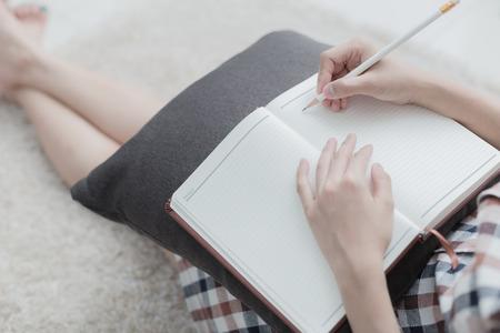 persona escribiendo: Joven y bella mujer escribiendo algo en el bloc de notas mientras está acostado en el piso en la sala de estar Foto de archivo
