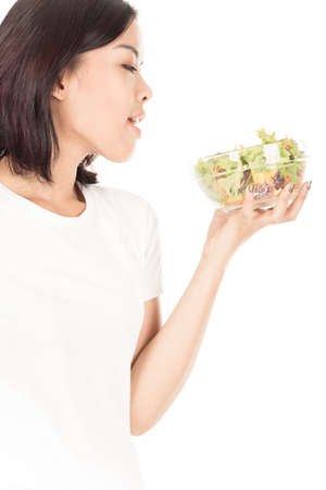 Portrait of a fit healthy hispanic woman eating a fresh salad isolated on white photo