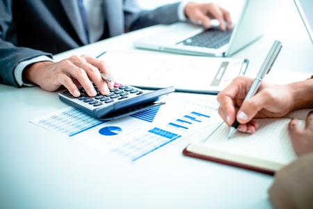 contabilidad financiera: La gente de negocios que discuten los cuadros y gráficos que muestran los resultados de su buen trabajo en equipo