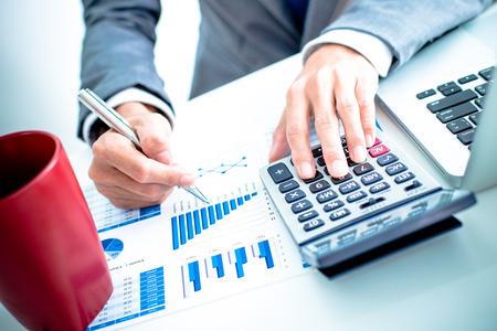 Empresário analisando gráficos de investimento com laptop. Contabilidade Imagens