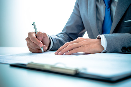 legal document: Hombre de negocios que se firma un contrato Foto de archivo