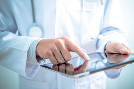 lekarz: Lekarz pracuje na cyfrowym tablecie Zdjęcie Seryjne