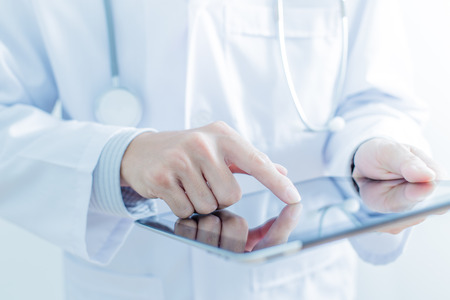 medical doctors: Doctor working on a digital tablet Stock Photo