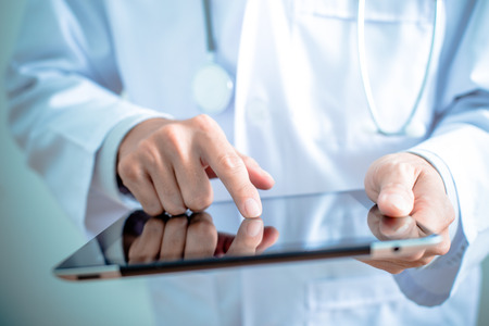 medical person: Doctor working on a digital tablet Stock Photo
