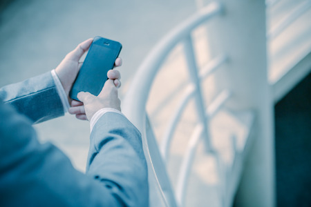 Young businessman using a phone sitting on the stairs photo