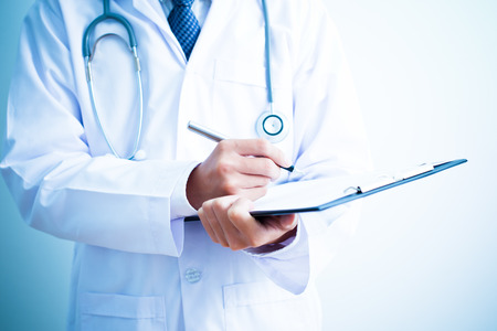 recetas medicas: Primer De Hombres Doctor rellenando el formulario m�dico Foto de archivo