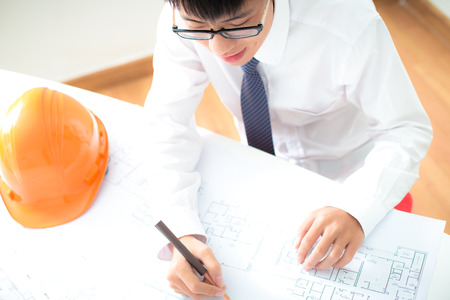 structural engineers: Closeup cropped image of a young male architect working on blueprints spread out on a table Stock Photo