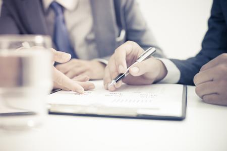 Man writing: Dos hombres de negocios que buscan en el informe y que tienen una discusi�n en el cargo.