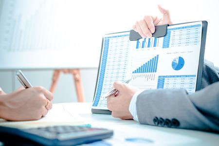 Executivos que discutem as paradas pessoas e gráficos que mostram os resultados de seu trabalho em equipe bem-sucedida