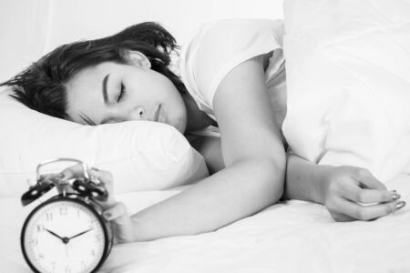 trying: Woman in bed trying to wake up with alarm clock Stock Photo