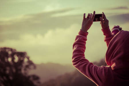 woman hiker taking photo with smart phone at mountain peak photo