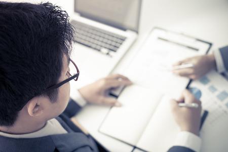 hombre escribiendo: Dos hombres de negocios que buscan en el informe y que tienen una discusión en el cargo.