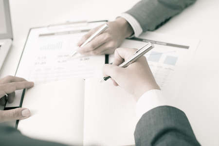 persuading: Two businessmen looking at report and having a discussion in office. Stock Photo
