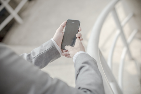 busy beard: Young businessman using a phone sitting on the stairs