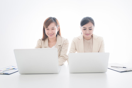 Two Pretty Smiling Businesswomen Discussing the Business using Laptop Device. photo