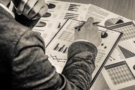 ペン及び業務報告書を持つ男の手。会計