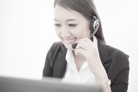 handsfree phones: businesswoman talking on the phone while working on her computer