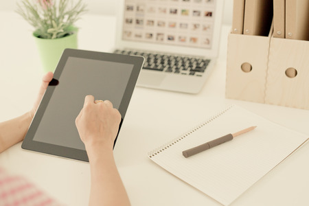 outwork: Woman on the workplace using a digital tablet