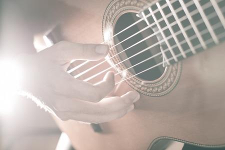 jugando: Practicar en tocar la guitarra. Apuestos j�venes que tocan la guitarra