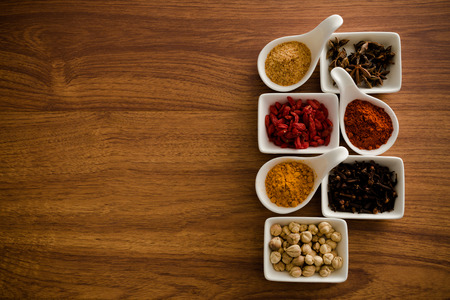 variability: Wooden table of colorful spices Stock Photo
