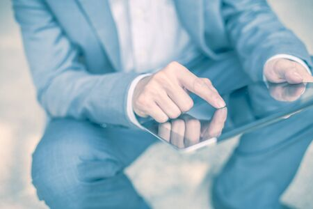 electronic organizer: Businessman using electronic tablet pc. He is sitting on a stairs. Stock Photo