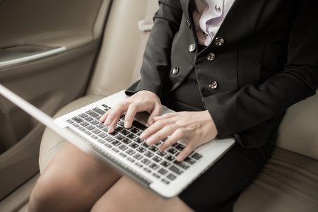 back seat: Young business using laptop in back seat of car Stock Photo