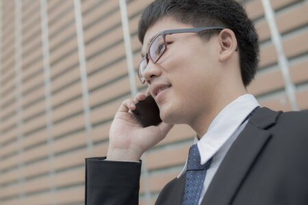 Young businessman using mobile phone, looking up photo