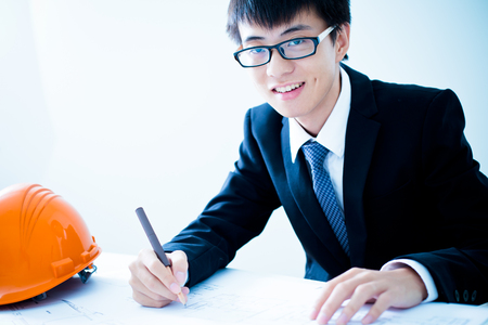 asian architect: Closeup cropped image of a young male architect working on blueprints spread out on a table Stock Photo