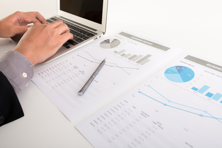 investment risks: Businessman analyzing investment charts with laptop. Accounting Stock Photo