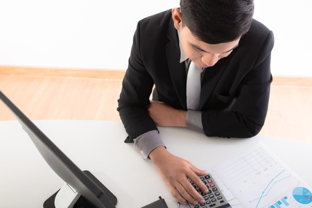 accounting: Businessman analyzing investment charts with laptop. Accounting Stock Photo