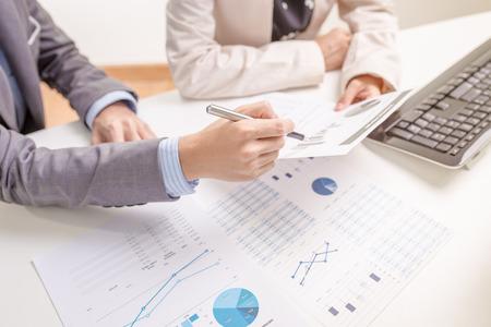 La gente de negocios en discusiones sobre los cuadros y gráficos que muestran los resultados de su trabajo en equipo éxito