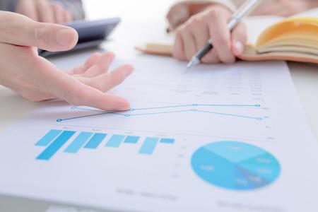 Les gens d'affaires discutant des tableaux et des graphiques montrant les résultats de leur travail d'équipe réussie Banque d'images