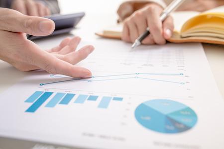 informe: La gente de negocios en discusiones sobre los cuadros y gráficos que muestran los resultados de su trabajo en equipo éxito