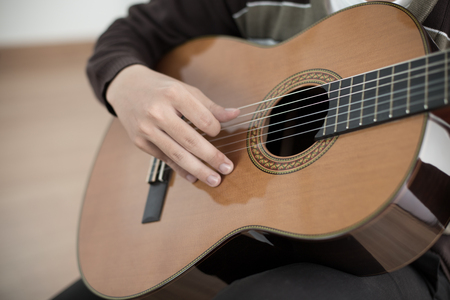 adult hand: Practicing in playing guitar. Handsome young men playing guitar