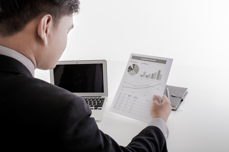 equities: Businessman analyzing investment charts with laptop. Accounting Stock Photo