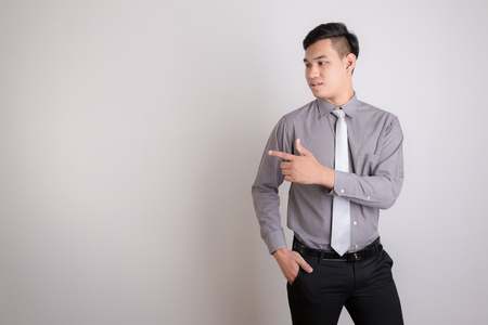 thai stretch: Handsome businessman pointing up, isolated on white background