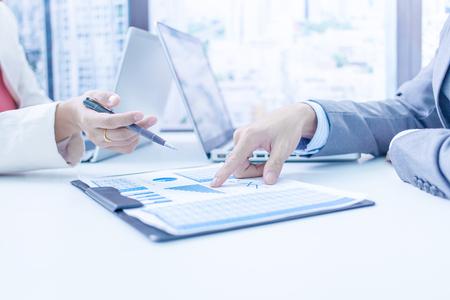 Les gens d'affaires discutant des tableaux et des graphiques montrant les résultats de leur travail d'équipe réussie