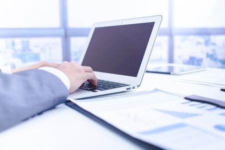 contabilidad: Negocios que analiza listas de inversi�n con el port�til. Contabilidad Foto de archivo