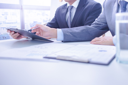 Two businessmen looking at report and having a discussion in office. Stock Photo