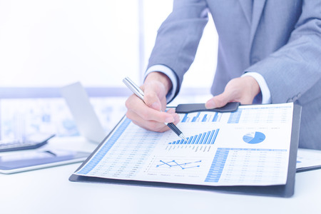analyzing: Businessman analyzing investment charts. Accounting