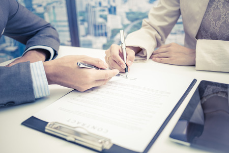 liability insurance: Female hand signing contract. Stock Photo