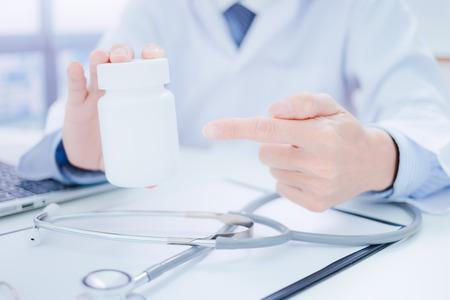 Doktor, der eine Flasche Pillen zum Patienten